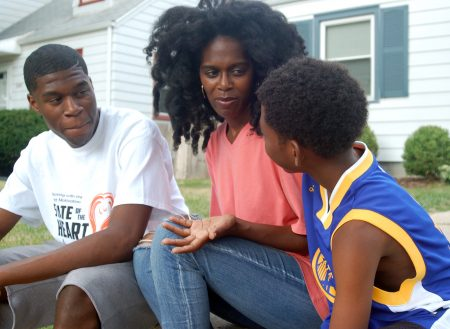 Brothers Isaiah Thornton, 18 (left) and J'Ali Thorton, 9, talk with their mother, Latrina Thornton, on their front walk. Photo by Andrea Waxman.
