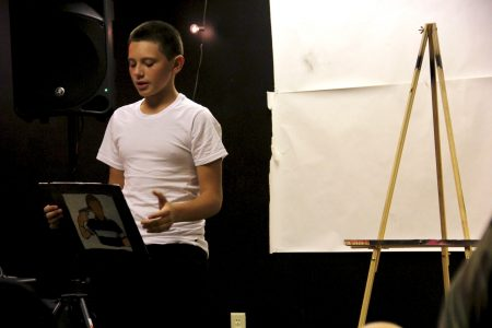 Andrew Reed, 14, a freshman at Milwaukee High School of the Arts, displays his painting and reads the accompanying poem. Photo by Rebecca Carballo.