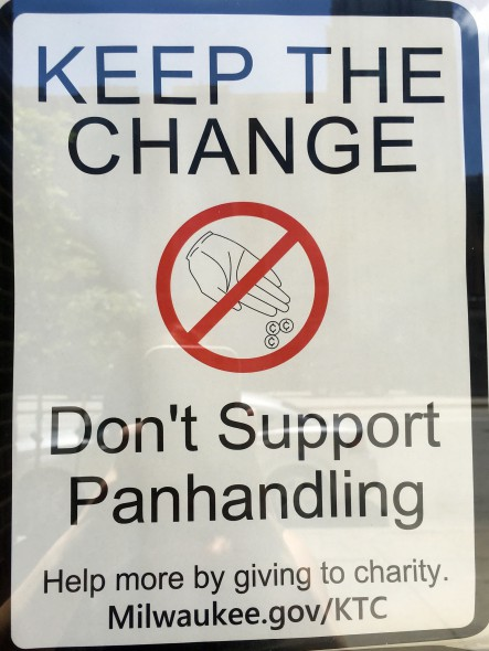 Local businesses hang signs in their windows to deter panhandling. Photo By Rebecca Carballo.