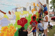 Community members fill in the outline painted by Tia Richardson, Jeanette Martín and Randy Flann. Photo by Rebecca Carballo.