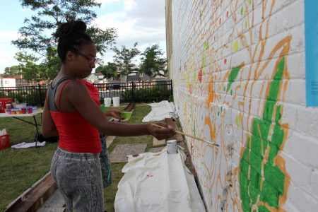 Artist Tia Richardson works on the mural. Photo by Rebecca Carballo.