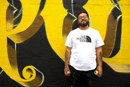 Chacho Lopez stands by his most recent mural in Walker's Point during an early stage in its creation. Photo by Emmy A. Yates.