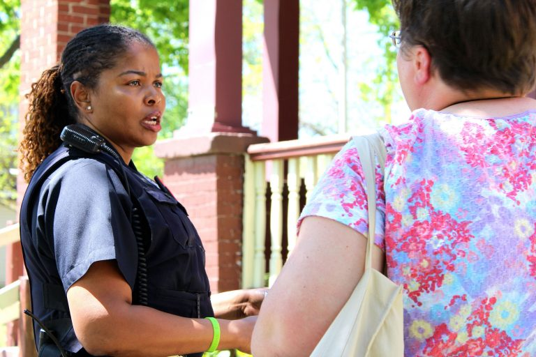 Milwaukee Police Department Community Liaison Officer Melissa Jones talks to a community organizer in the Midtown neighborhood. Photo by Mark Doremus.