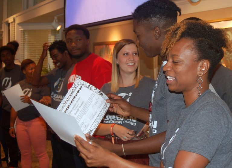 Sharlen Moore (right), Urban Underground director, presents certificates, as project editor Allison Dikanovic, (third from right), congratulates participant Donald Beamon. Photo by Andrea Waxman.