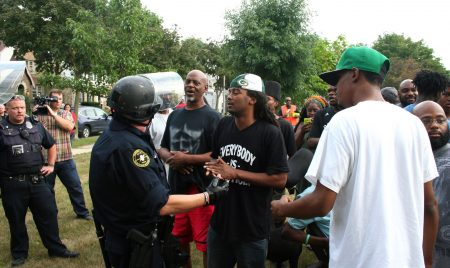 Frank Sensabaugh speaks with a police officer before a young man was taken into police custody without incident. Photo by Jabril Faraj.