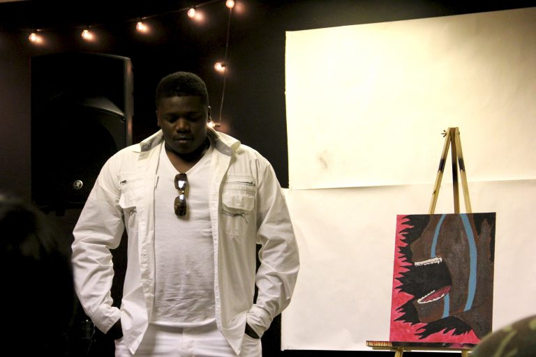 Stephan Bell, 17, a James Madison High School senior, presents his painting and poem at TRUE Skool's summer showcase. Photo by Rebecca Carballo.