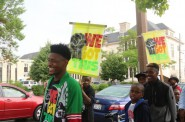 """Participants in """"We Got This"""" march with handmade signs down Dr. Martin Luther King Drive during the 14th Annual Summer of Peace Rally. Photo by Amelia Jones."""