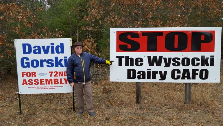 """David Gorski is running as a Democrat for the 72nd Assembly District. He is seen here with a sign opposing the Golden Sands Dairy, which has been proposed by the Wysocki Family of Cos., which also owns the Central Sands Dairy. On his Facebook page, Gorski said: """"We all want businesses to grow, but one business shouldn't be allowed to harm the health and property value of its neighbors."""" Photo courtesy of David Gorski."""
