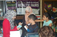 A family checks in at the South Division High School health fair. Photo by Clara Hatcher.