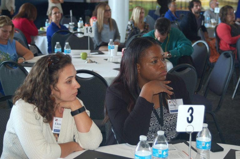 Safe & Sound's Elena Burke (left), Drug Free Communities manager and Adrian Spencer, District 5 community organizer, listen to a panel of neighborhood organization directors. Photo by Andrea Waxman.