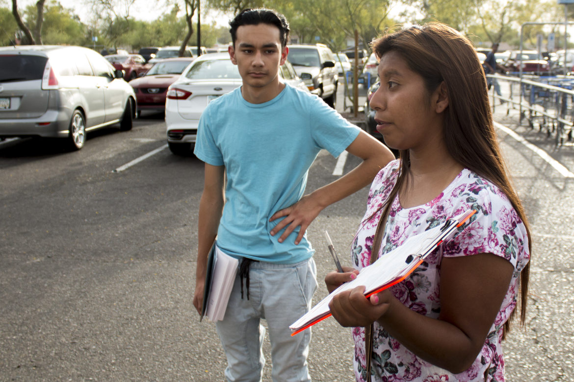 Yenni Sanchez, 18, has registered people to vote for three years. Daniel Flores, 16, is also a volunteer. They are signing up voters at a Wal-Mart parking lot in Phoenix. Photo by Courtney Columbus of News21.