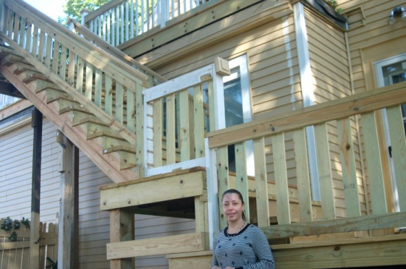 Maria Alvarado stands at the base of the staircase and upper deck built with funds provided by the Department of Neighborhood Service's Code Loan Program. Photo by Edgar Mendez.