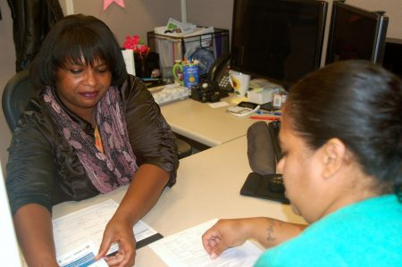 Vanessa Burkett provides Lizbeth Estrada with information about the energy assistance program. Photo by Brittany Carloni.