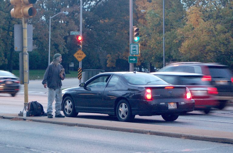 "A panhandler on a Capitol Drive median at Humboldt Avenue holds a sign that says ""Hungry."" Photo by Andrea Waxman."