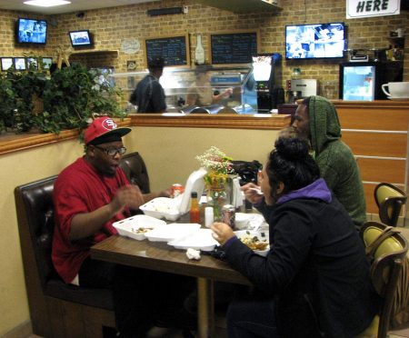 Shannon Reyes (left), Andre Moore and Abigail Velazquez eat dinner at Daddy's Soul Food and Grille. Photo by Clara Hatcher.