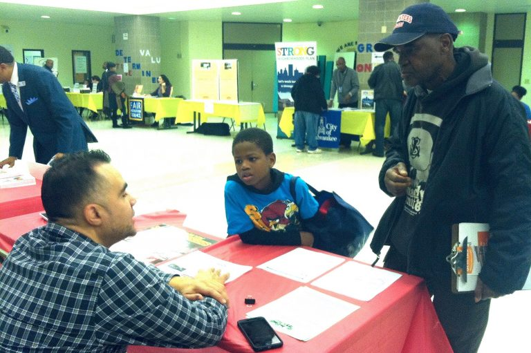 Bert Simmons and his son, Quavon Pollard, get information on housing loans at the housing resource fair. Photo by Clara Hatcher.