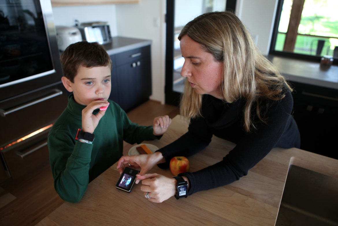 Jack Christensen, 8, has an after-school snack at his home in Waunakee, Wis. His mother, Jess Franz-Christensen, logs his carbohydrate intake on a monitoring device. Jack has Type 1 diabetes. An investigation by Wisconsin Health News, the Wisconsin Center for Investigative Journalism and Wisconsin Public Radio found the cost of seven widely prescribed drugs has risen between 29 percent and 5,241 percent since 2011. Photo by Coburn Dukehart of the Wisconsin Center for Investigative Journalism.