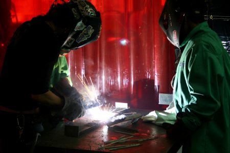 Jennifer Kessenich (left) demonstrates welding, as Bradley Tech freshman Zantrell Irvin looks on. Photo by Jabril Faraj.