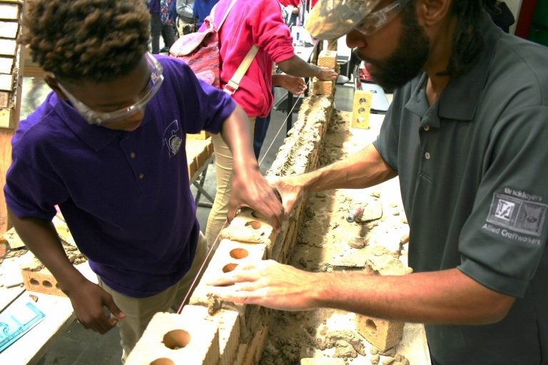 Tim Brown (right) helps a student lay a brick during the event. Photo by Jabril Faraj.