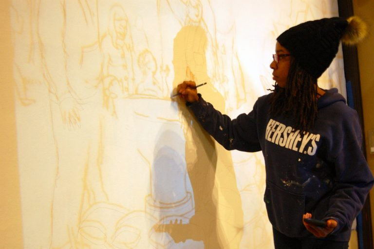 Tia Richardson traces the outline of a mural she is working on at All People's Church. Photo by Brittany Carloni.