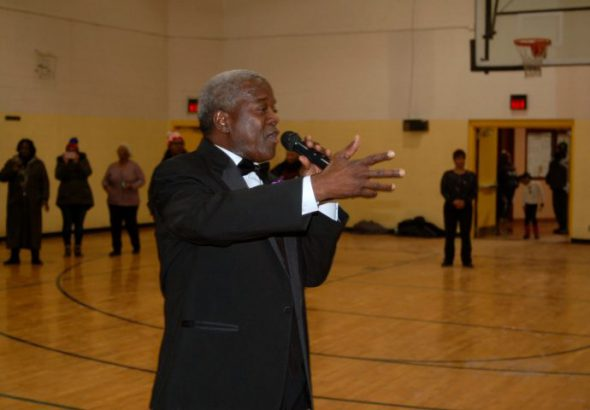 Andre Lee Ellis welcomes 500 men and boys in tuxedos at the start of the program at Northcott Neighborhood House. Photo by Andrea Waxman.