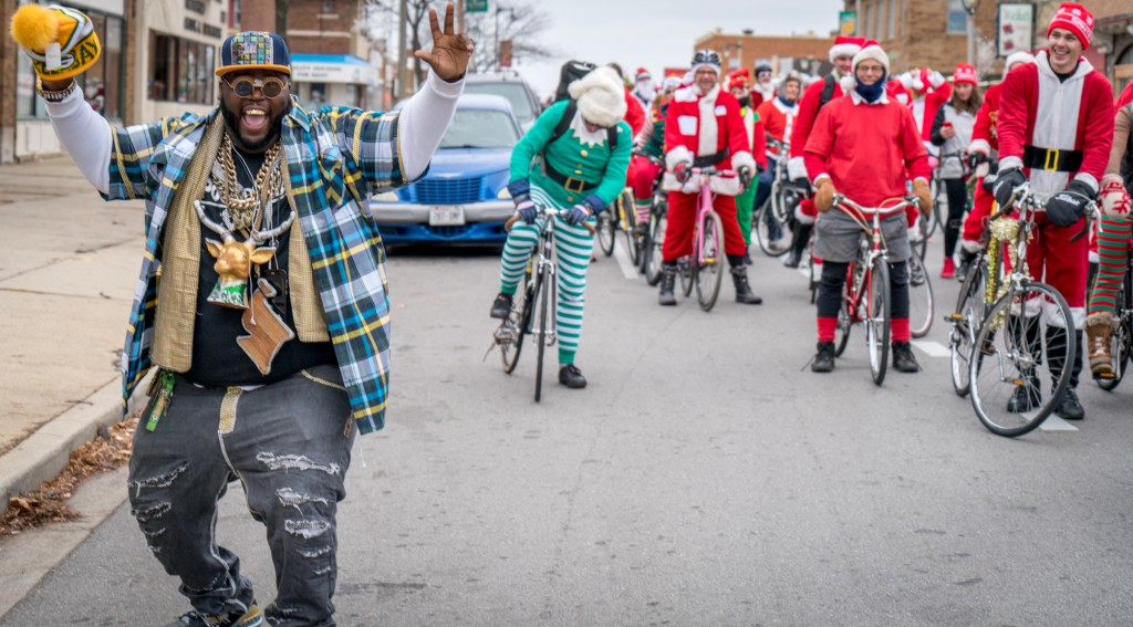 "Stephen ""Kingjuice"" Jackson cheers on the Santa Rampage outside Sho-N-Out Barbershop at 55th and North Ave. I live nearby, and I'd like to give a shout out to King Juice for putting some joy in my heart every time I ride by and see his smiling face and Juicewear."