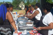 Volunteers serve a free meal during a community event at Moody Park in June.(Photo by Edgar Mendez.