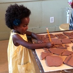 A little girl inscribes her message on a clay stone during Doors Open Milwaukee, where 263 visitors participated in the ongoing Walls of Strength project. Photo courtesy of Lori Gramling.