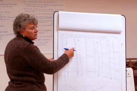 Alicia Modjeska, chief administrative officer of the Behavioral Health Division, shows attendees a rough sketch of a possible floor plan for the facility. Photo by Naomi Waxman.