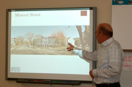 Bob McCormick, director of property management at Cardinal Capital, Inc., displays a digital rendering of the proposed apartment building on the northeast corner of W. Mineral and S. 24th streets. Photo by Naomi Waxman.