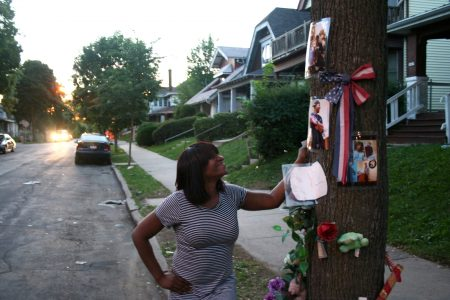 Raquel Russell stands by the memorial for her son who was shot and killed in November 2015. Photo by Jabril Faraj.