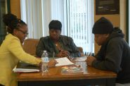 Kori Ashley, staff attorney for Legal Action, helps Maleek Bledsoe review his juvenile record as his mother looks on. Photo by Edgar Mendez.