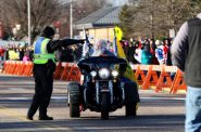 A police officer directs former state Sen. Dave Zien where to park his motorcycle as a crowd waits outside of Memorial High School to see presidential candidate Donald Trump speak April 2 in Eau Claire. Trump is among the candidates whose campaigns owe communities in Wisconsin thousands of dollars for police protection in 2016, according to an investigation by the Center for Public Integrity. Photo by Marisa Wojcik of the Eau Claire Leader-Telegram.