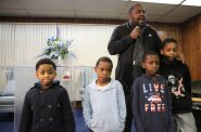 Tory Lowe helped to organize a meeting about lead in drinking water at the House of Prayer in Milwaukee on Dec. 6. He asked the young boys in the audience to join him at the front of the room to challenge everyone to protect them from the dangers of lead in drinking water. The children, from left, are Tomairus Brown, 5, Diamante Silas, 7, Jakoda Eiland, 8, and Jeriko Eiland, 11. Photo by Coburn Dukehart of the Wisconsin Center for Investigative Journalism.