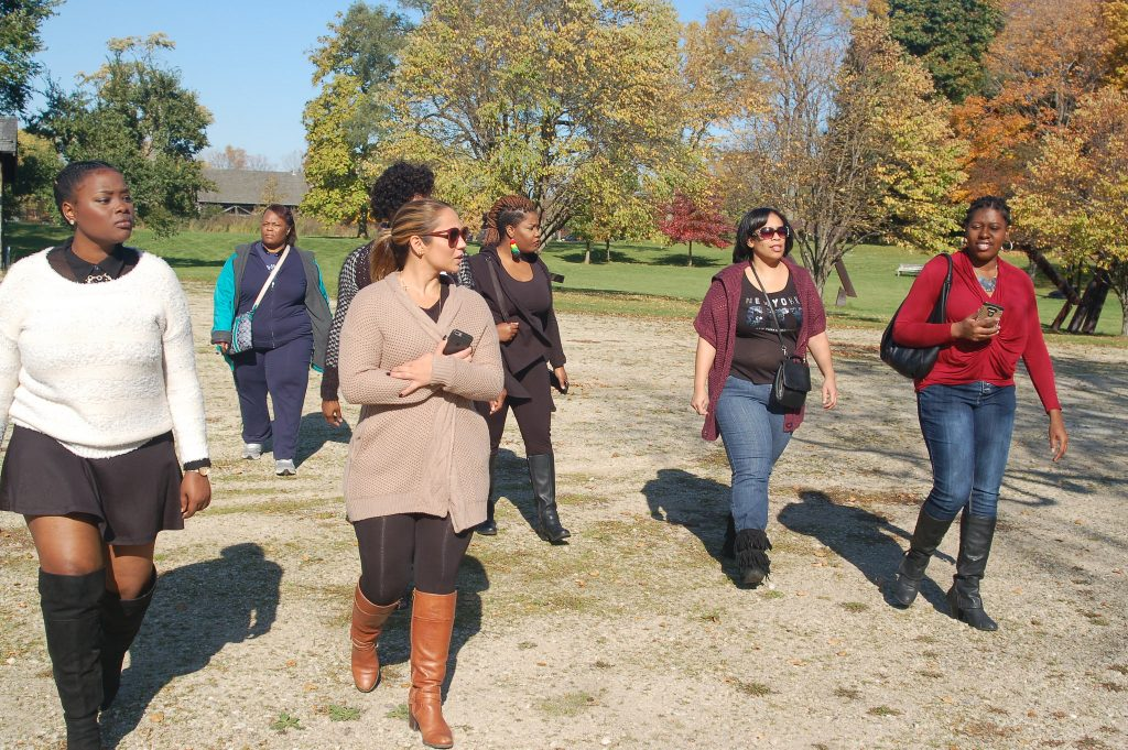 "Participants in Social X's trip to Lynden Sculpture Garden enjoy the lush surroundings as they walk toward afro-futurist artist Fo Wilson's installation, ""Eliza's Peculiar Cabinet of Curiosities."" Photo by Naomi Waxman."