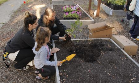 Danielle Nabak (holding plant) works with a mother and her daughter in a garden bed. Photo courtesy of Kelsey Jorissen.