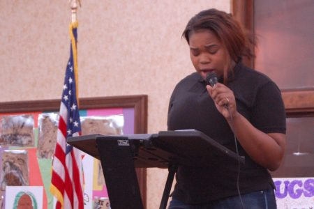 """Alexia Evans reads her poem """"You Don't Live on My Street"""" at the summit. Photo by Camille Paul."""