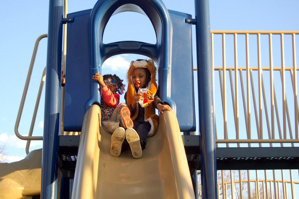 Dezaray Bivens (left), 4, and Lazaya Thomson, 8, play on the slides in Johnsons Park. Photo by Camille Paul.