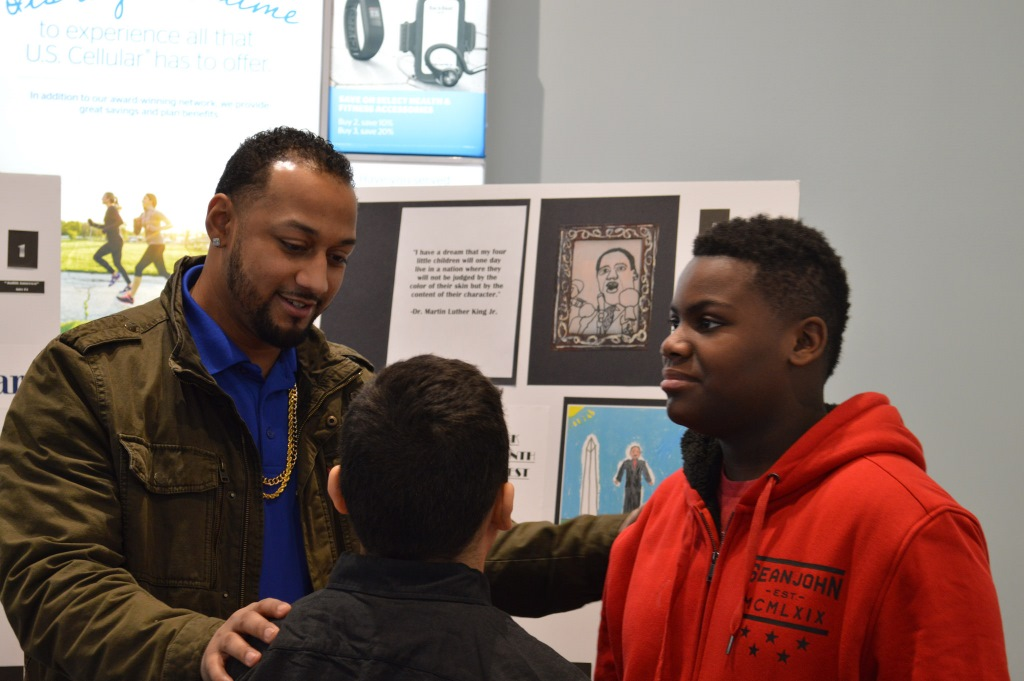 Vedale Hill (left) speaks to Xzavier Ledesma (back to camera) and Lamarr Hughlett about their artwork. Photo by Alexandria Bursiek.