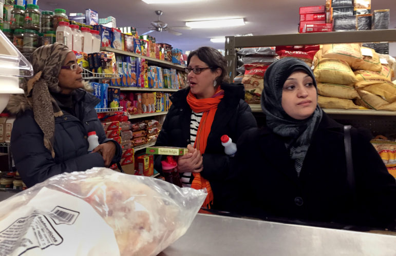 Rihab Taha, left, a caseworker for Jewish Social Services who came as an immigrant from Sudan; Becca Schwartz, resettlement coordinator for JSS; and Rula, a newly arrived refugee from Syria, shop at Istanbul Market in Madison, Wis., Jan. 31, 2017. Rula and her family came to Madison just one week before President Donald Trump indefinitely halted all refugee immigration from Syria. Photo by Dee J. Hall of the Wisconsin Center for Investigative Journalism.