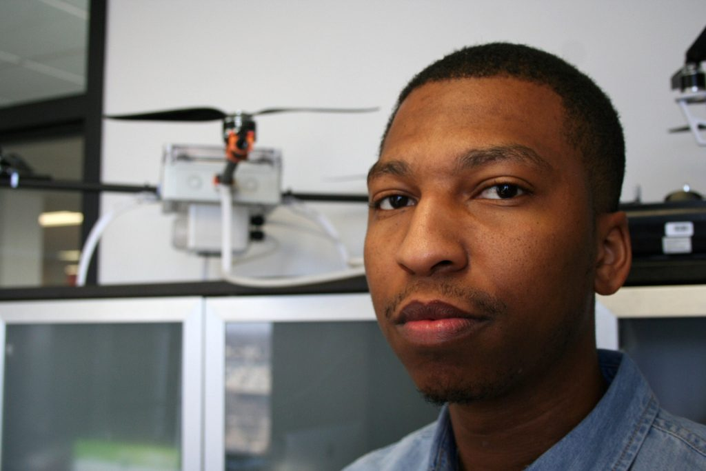 Qaiyim El-Amin stands in front of his specialized water-sampling drone. Photo by Jabril Faraj.