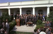 President Lyndon B. Johnson signs the Poverty Bill (also known as the Economic Opportunity Act) while press and supporters of the bill look on, August 20, 1964. Photo is in the Public Domain