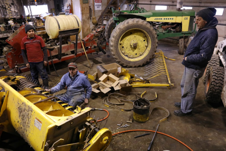 Roberto, left, a Mexican immigrant employeed at Rosenholm farm in Cochrane, Wis., works in the machine shop with Gerald Thaldorf, center, while talking to owner John Rosenow. Rosenow says the dairy industry in Wisconsin would be crippled without immigrant workers. Photo by Coburn Dukehart of the Wisconsin Center for Investigative Journalism.