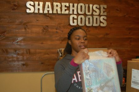 Takeya Hibbler wraps consignment items for shipping. Photo by Andrea Waxman.