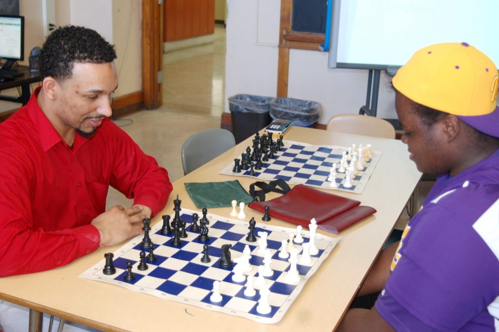 Davontae Franklin (right), a junior at Washington High School, plays against his head coach, Micheal Moore, in a friendly game of chess. Photo by Dean Bibens.