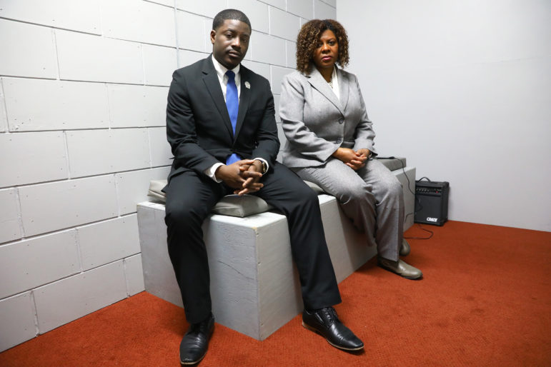Rep. David Crowley, D-Milwaukee and Sen. LaTonya Johnson, D-Milwaukee, are seen in a life-sized mock solitary cell that was set up at the Wisconsin State Capitol. On March 30, Sen. Johnson announced the introduction of legislation that would prohibit the placement of inmates living with serious mental illnesses in solitary confinement for more than 10 days. The legislation would also require that a mental health evaluation be performed on any inmate before he or she is placed in solitary confinement. Photo by Coburn Dukehart of the Wisconsin Center for Investigative Journalism.
