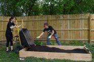 Melissa Graham dumps soil in the garden bed while Nichole Logan spreads the soil. Photo by Alexandria Bursiek.