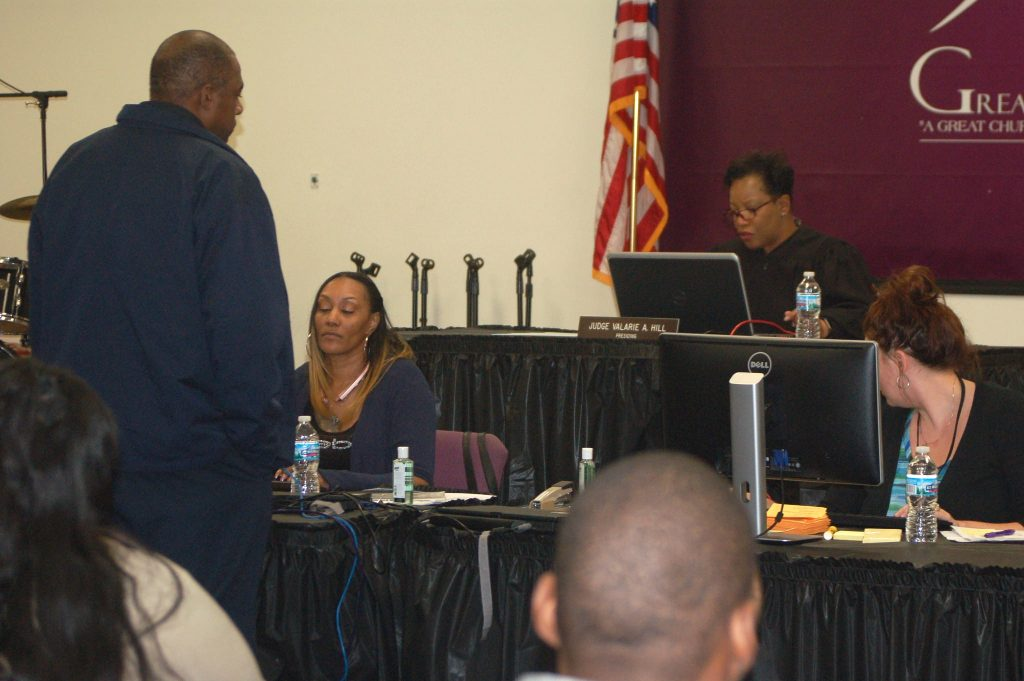 A defendant comes before Municipal Judge Valarie Hill in a meeting room converted into a courtroom at Greater New Birth Church, 8237 W. Silver Spring Drive. Photo by Edgar Mendez.