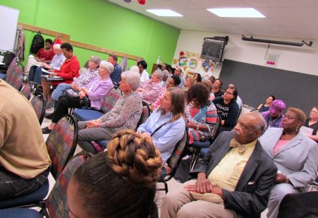 "Residents and community representatives, including ""Dr."" Lester Carter (far right), pack a room in the COA Goldin Center. Photo by Jabril Faraj."