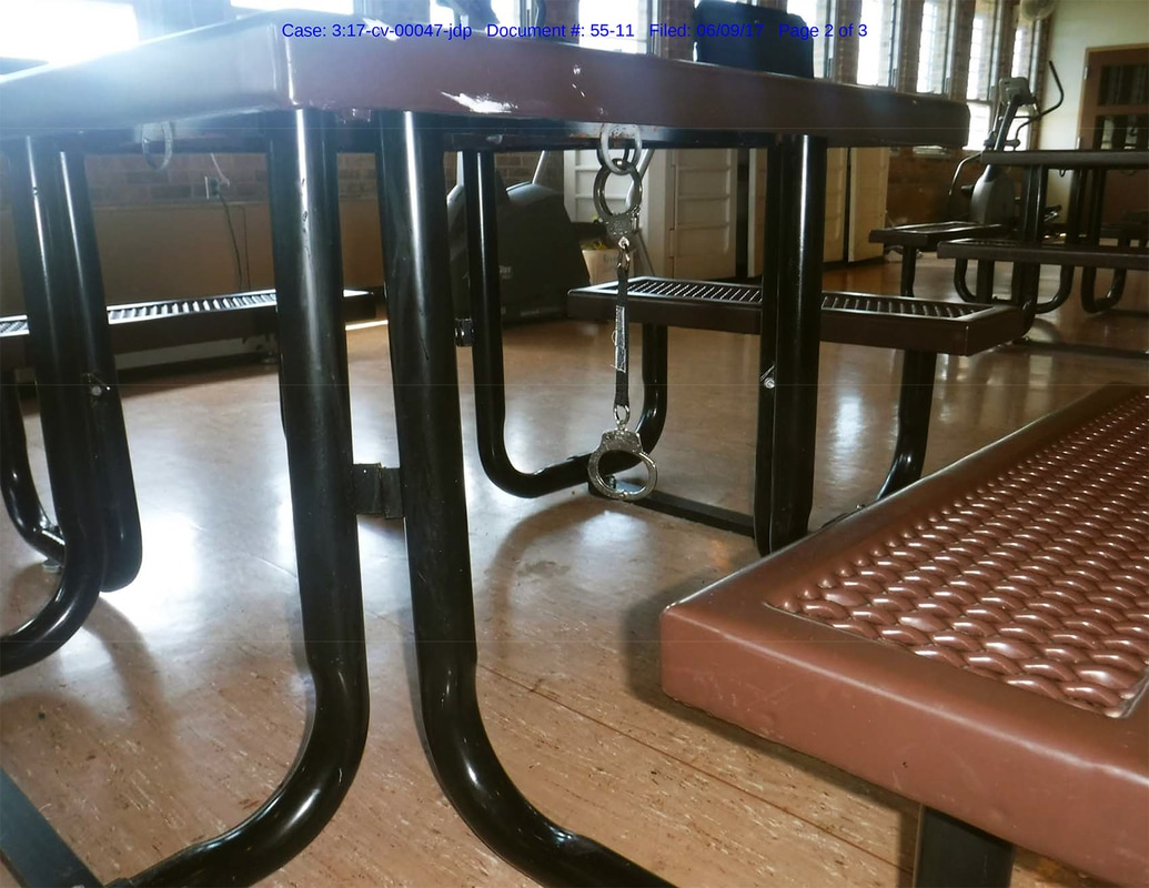 This picture shows a tether and handcuff set dangling from a table in the security unit.